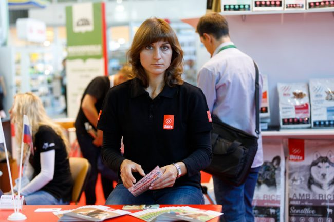 Женщина на выставке корма