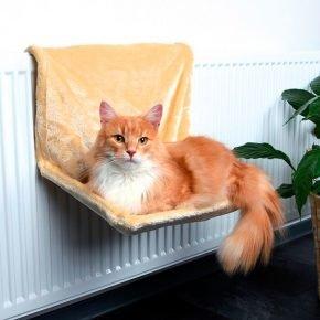 рыжий кот лежит в светлом плюшевом гамаке, подвешенном на пластинчатом радиаторе отопления