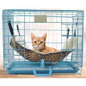 кот лежит в двустороннем гамаке из флиса, подвешенном на карабинах за верхние прутья клетки с четырёх сторон