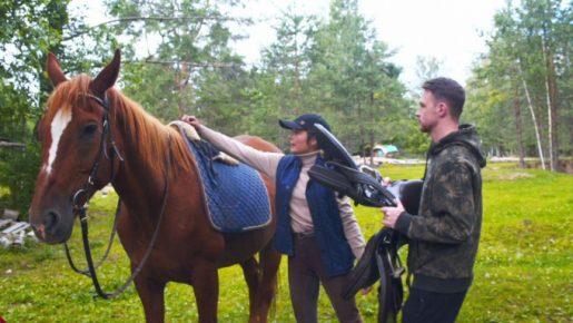 Инструктор седлает лошадь