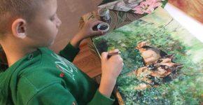 Мальчик рисует животных